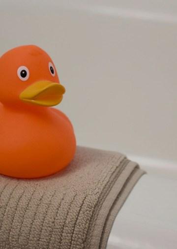 orange rubber ducky on a brown bath mat