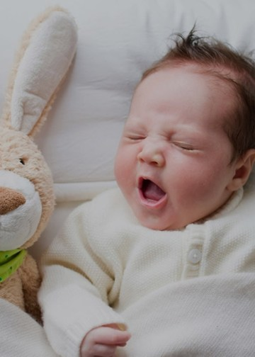Baby sleeping next to a bunny rabbit