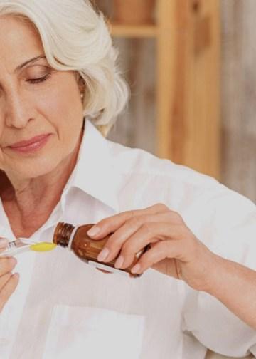 elderly woman taking iron on a spoon