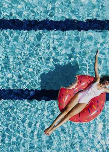 woman on a donut inflatable in a pool