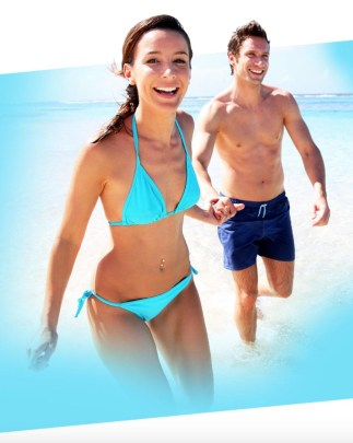 happy fit couple running in the beach
