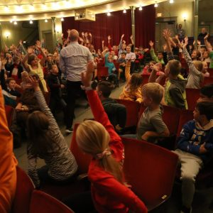 kids enthusiastically raising their hands during an event at the ramsdelll theatre