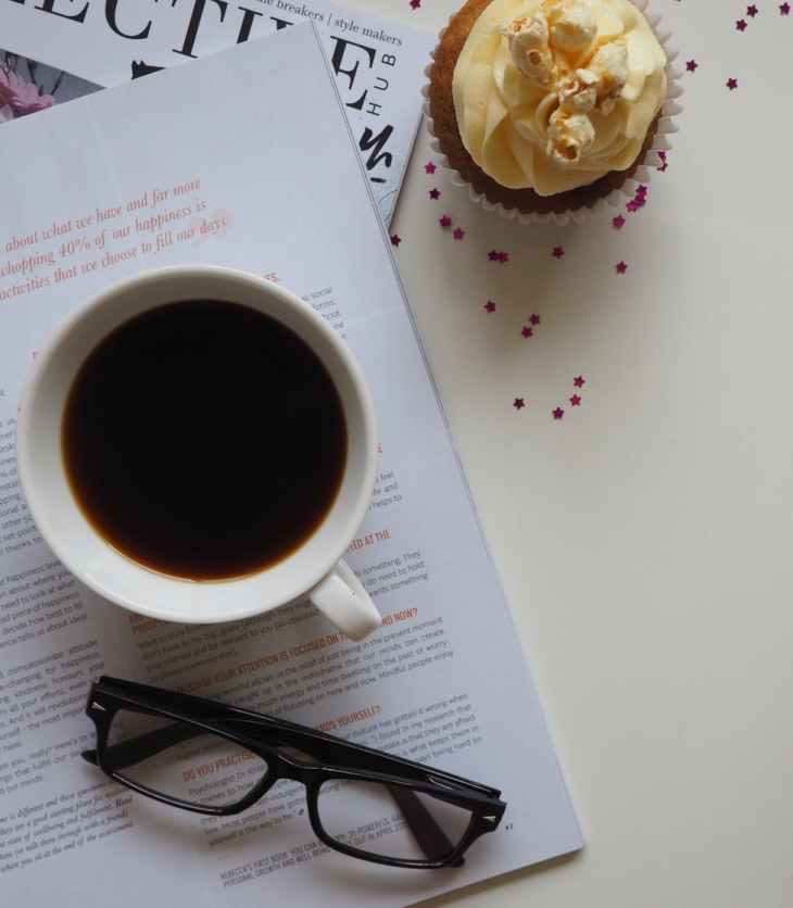 white ceramic cup with coffee on top of opened book and near eyeglasses