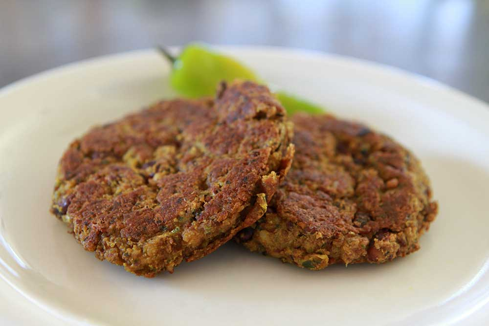 Two black bean burgers with pickled pepper