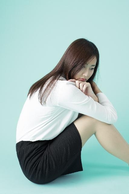 膝を抱えて悩む女性