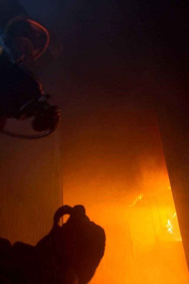 Firefighter inside a burning house