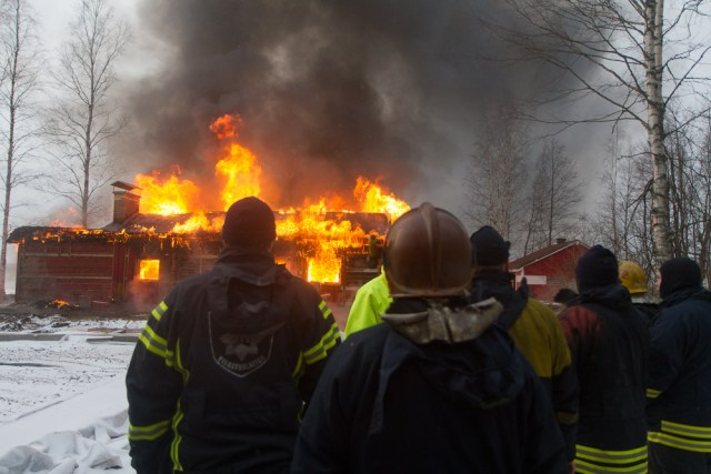 firefighters watching a house burn during an exercise