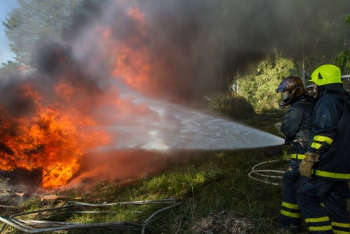 firefighter spraying water on burning building