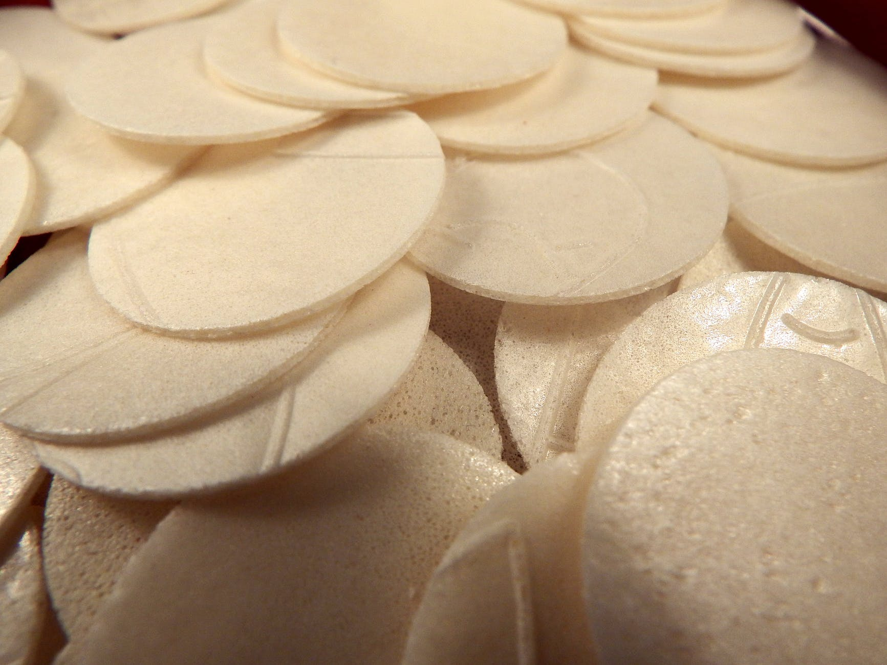 pile of thin white circles of sacramental bread