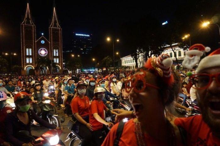 Nochebuena en Ho Chi Minh. Muchas motos y la catedral Notre Dame iluminada al fondo