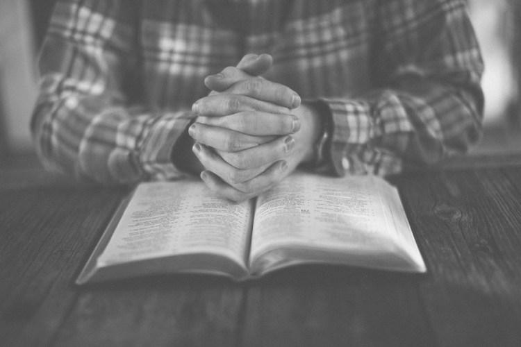 Prayer, hands folded on open Bible