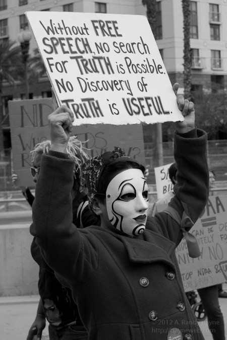 Masked protester holding a sign above their head.