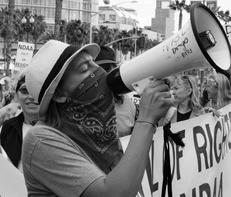Protester in a mask yelling through a bullhorn.