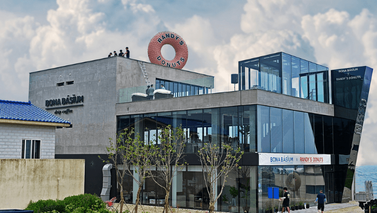 Exterior of Randy's Donuts South Korea location with a giant rooftop donut