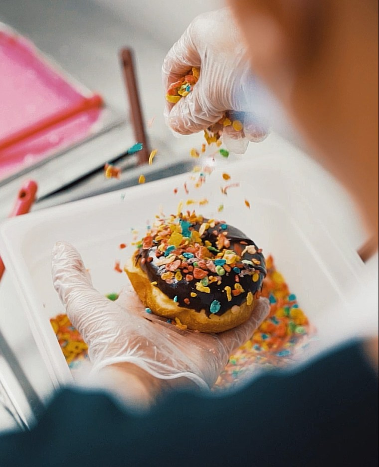 Fruity Pebbles being sprinkled on chocolate raised Randy's donut
