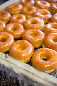 Rows of Randy's glazed donuts cool on rack during preparation