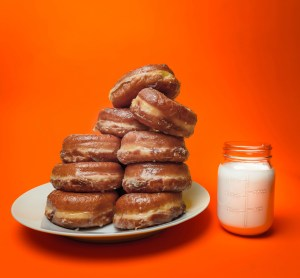 Two stacks of Randy's glazed donuts on a plate with a mason jar full of milk beside it