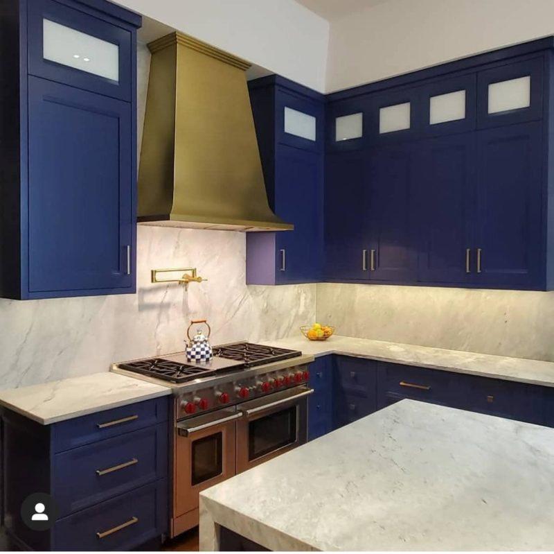 blue kitchen with gold range hood