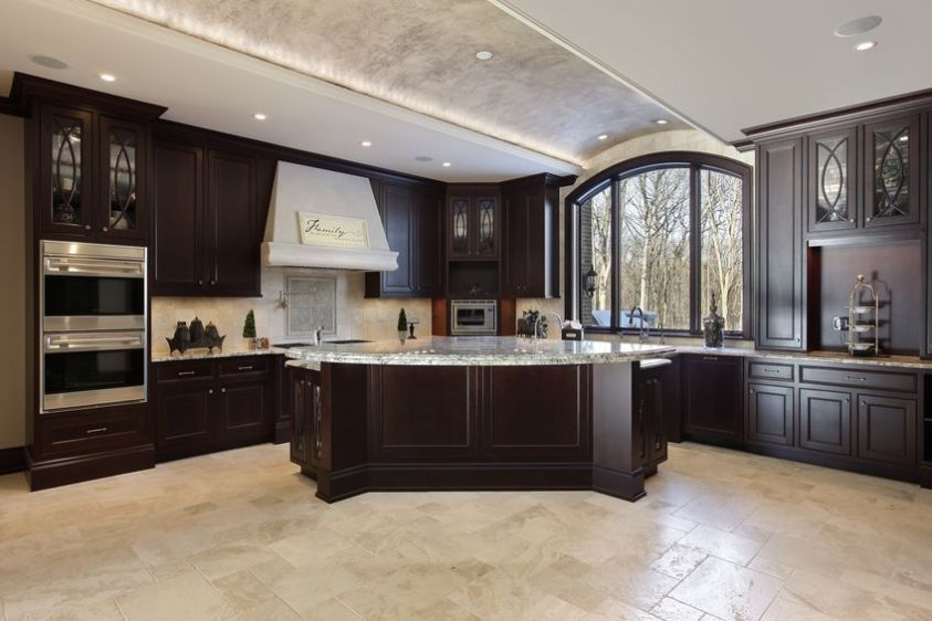 large kitchen in luxury home with dark wood cabinetry