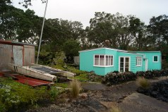 A bach with a boat shed at Rangitoto Wharf
