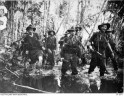1942-12. PAPUA. BUNA. AUSTRALIAN TROOPS OF 2/7TH CAVALRY REGIMENT AT CAPE ENDAIADERE ADVANCE THROUGH MUD AND SLUSH ON BUNA. FRONT LEFT IS DAVE HERBERT, BEHIND HIM AT FAR REAR IS FRED OUGHTON, SECOND FROM RIGHT BILL PATON AND FAR RIGHT BLUE DAWSON.