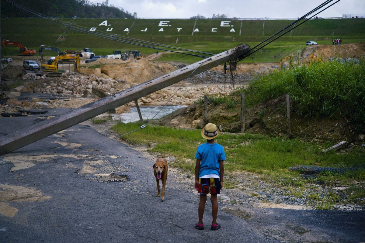 A boy accompanied by his dog watches the repairs of Guajataca Dam, which cracked during the passage of Hurricane Maria, in Quebradillas, Puerto Rico, Tuesday, Oct. 17, 2017. The dam was built around 1928, and holds back a man-made lake. (AP Photo/Ramon Espinosa)