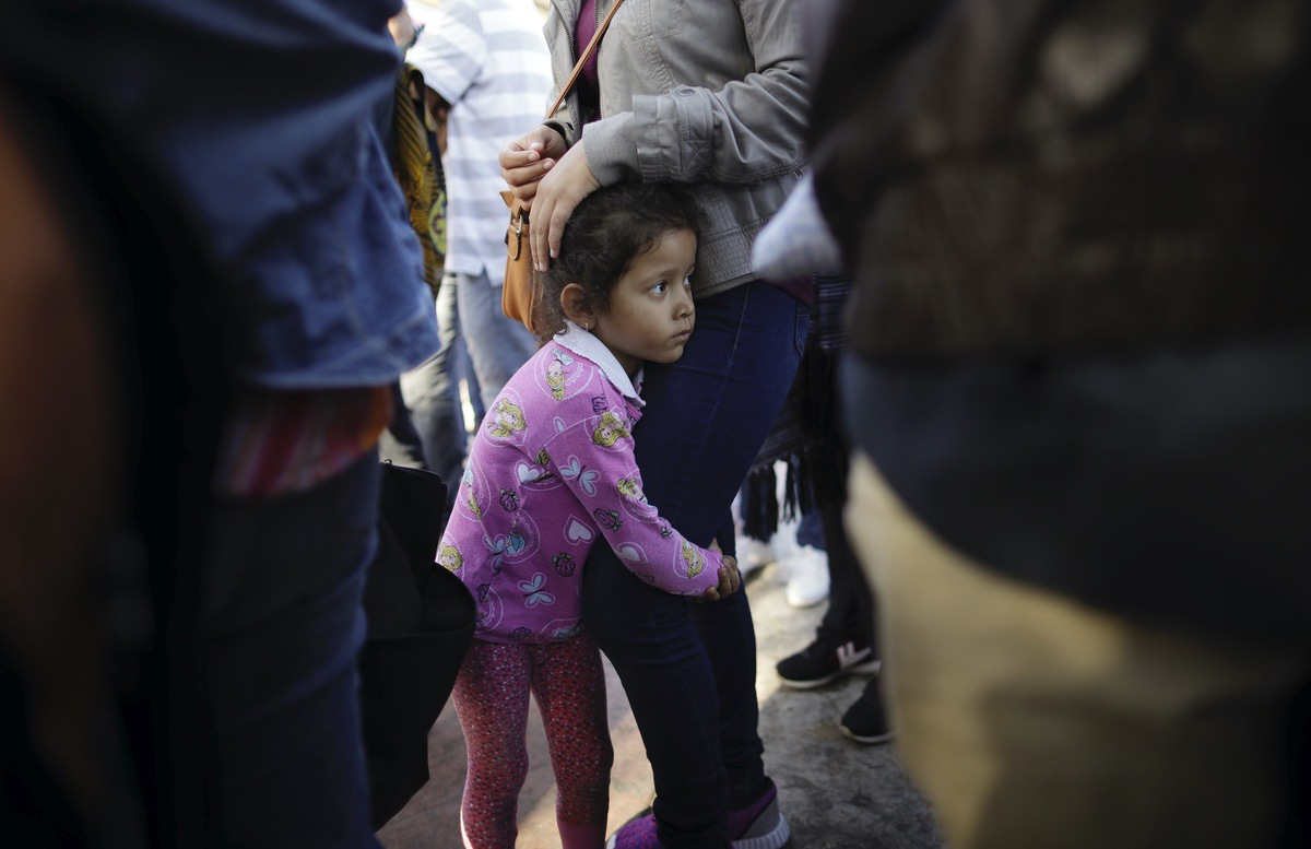 In this June 13, 2018 photo, Nicole Hernandez, of the Mexican state of Guerrero, holds on to her mother as they wait with other families to request political asylum in the United States, across the border in Tijuana, Mexico. (AP Photo/Gregory Bull)