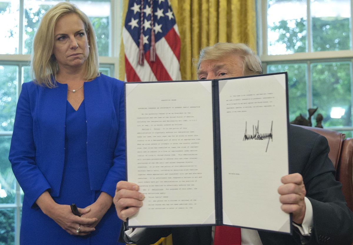 President Donald Trump holds up an executive order he signed to end family separations, during an event in the Oval Office of the White House in Washington, Wednesday, June 20, 2018. Looking on is Homeland Security Secretary Kirstjen Nielsen, left. (AP Photo/Pablo Martinez Monsivais)