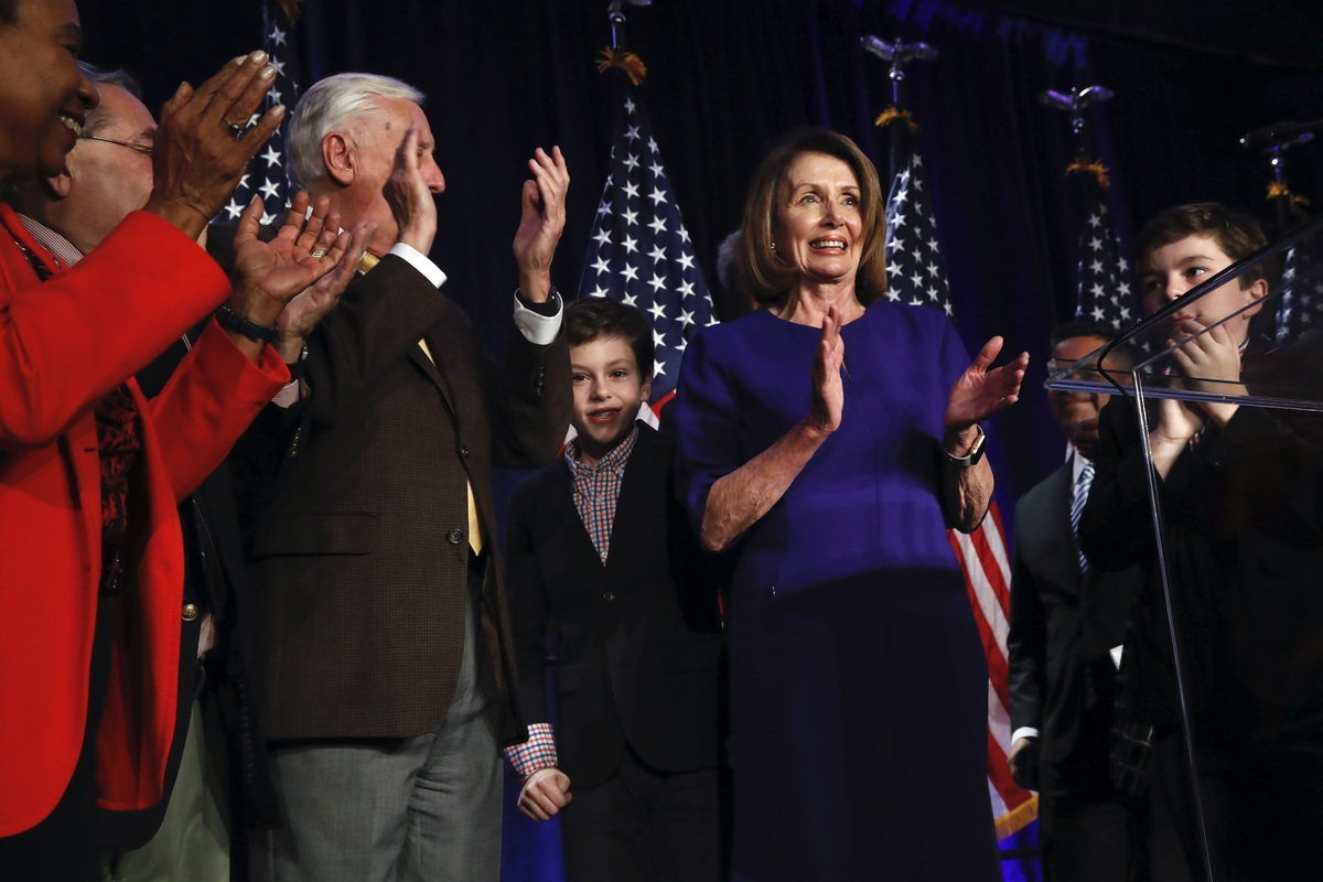 Nancy Pelosi of Calif., right, claps between her two grandsons on stage with House Democrats after speaking about Democratic wins in the House of Representatives to a crowd of Democratic supporters during an election night returns event at the Hyatt Regency Hotel, on Tuesday, Nov. 6, 2018, in Washington. (AP Photo/Jacquelyn Martin)