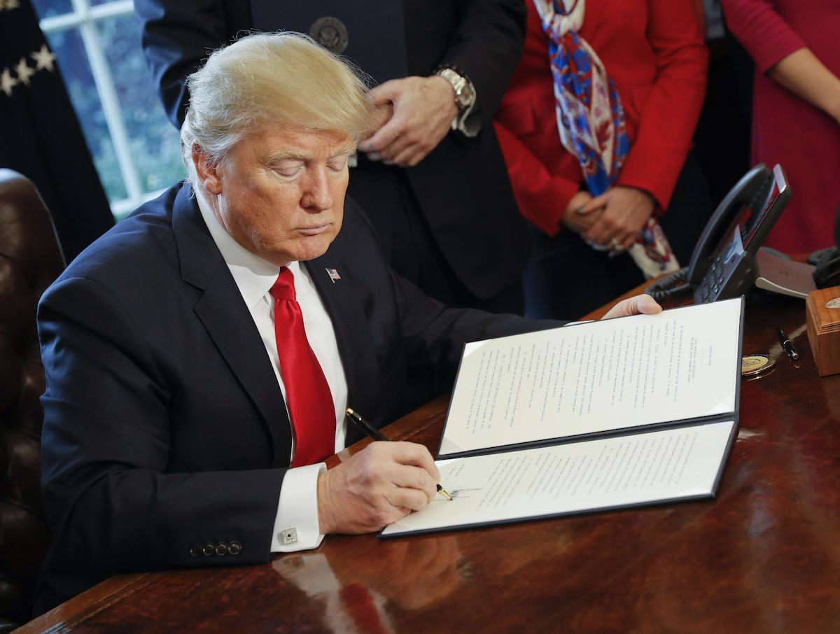 Donald Trump signs an executive order (AP)