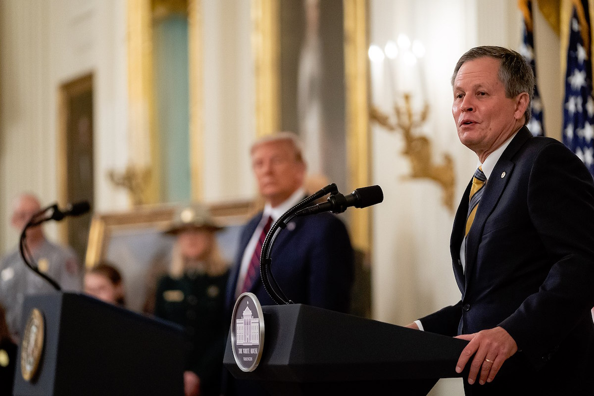 President Donald J. Trump listens as Senator Steve Daines, R-Mont., delivers remarks prior to President Trump's signing of H.R. 1957- The Great American Outdoors Act Tuesday, August 4, 2020, in the East Room of the White House. (Official White House Photo by Tia Dufour)