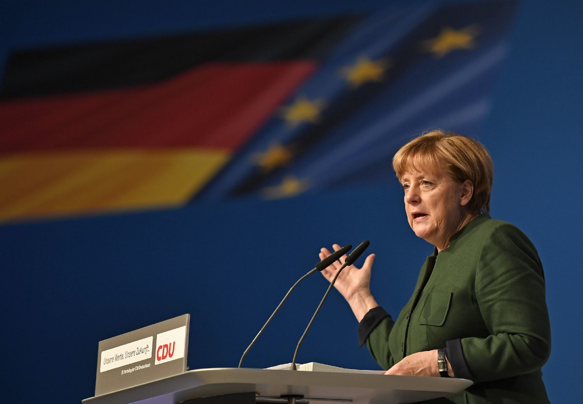 German chancellor Angela Merkel speaks in front of the national flag at the general party conference of the Christian Democratic Union, CDU, in Essen, Germany, Wednesday, Dec. 7, 2016. (AP Photo/Martin Meissner)