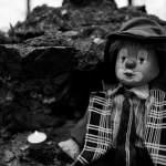 Horrorclown-Puppe wartet in einer Burgruine - schwarzweiss