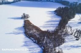 Halbinsel im zugeschneiten Amsoldingersee von oben aus der Luft