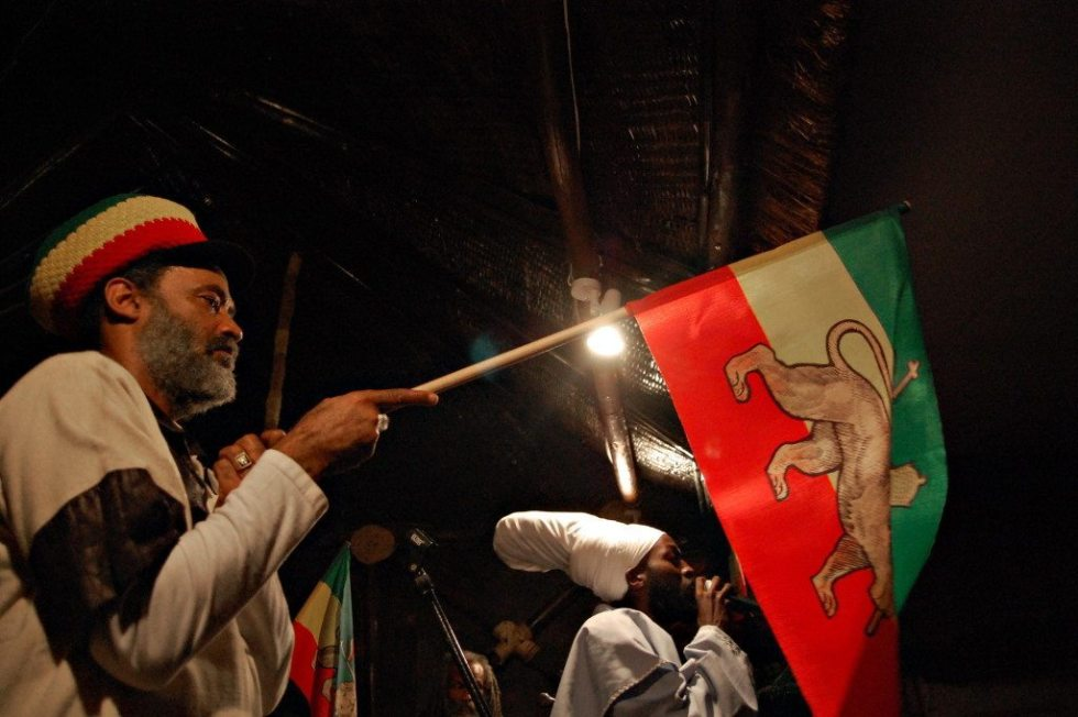 A Rasta man holds the former Ethiopian flag with the golden crowned lion, a version used during the reign Ethiopia's last emperor Haile Selassie, at a local restaurant in Addis Ababa on November 1, 2009. The magnificent coronation ceremony for Ethiopia's last emperor Haile Selassie had a global impact, but 80 years on fewer than 100 people gathered to mark its anniversary. No official celebrations have been organised in Ethiopia -- just a few dozen Rastafarians and some of Selassie's former aides and officers met in a cultural centre in Addis Ababa.The participants gave their memories of Selassie to a background of reggae music, while outside some children watched the ceremony with curiosity. AFP PHOTO/Aaron MAASHO (Photo credit should read AARON MAASHO/AFP/Getty Images)