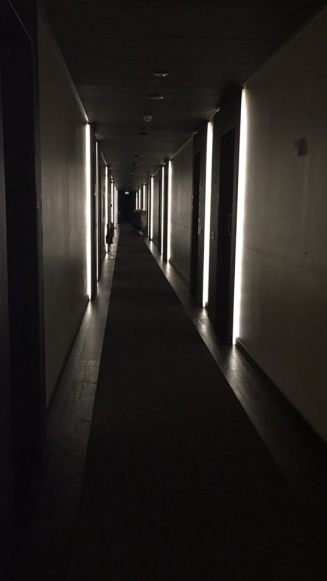 Dark corridor to room with # illuminated