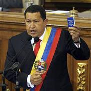 15日、ベネズエラの首都カラカスで、憲法を手に議会で演説するチャベス大統領(ロイター=共同)