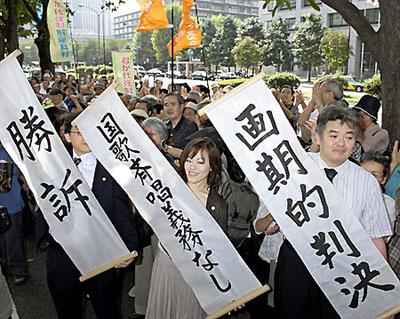 国旗、国歌の強制を違法とした判決に、垂れ幕を掲げ喜ぶ原告団と支援者ら=21日、東京・霞ヶ関の東京地裁前〔共同〕