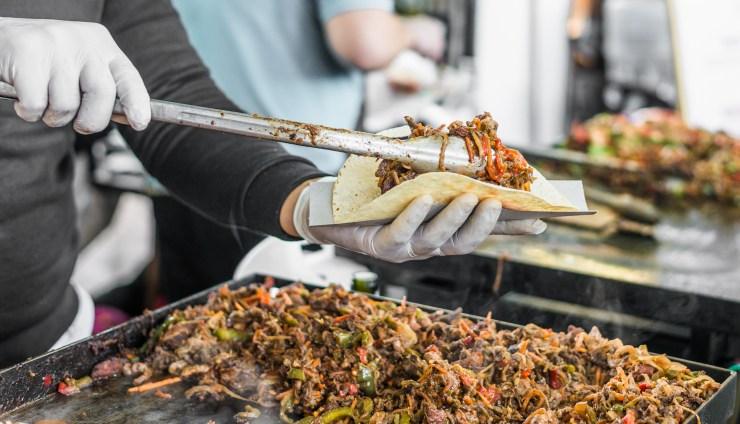 Chef at a street food market preparing a taco