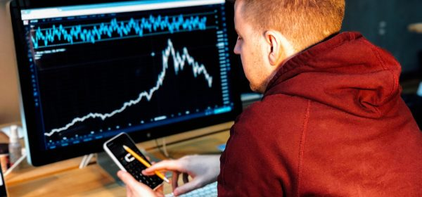 Man looking at his phone with stock market chart showing