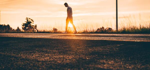 Man looking down while walking on a road during sunset