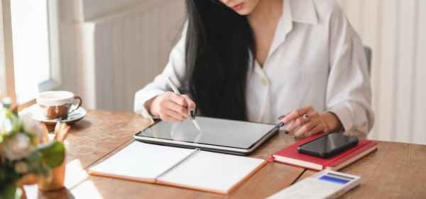 person writing on tablet computer