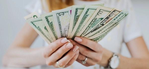 woman holding fan of dollar bills