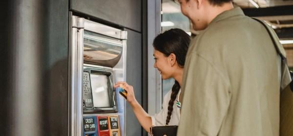 content couple using ticket machine in underground