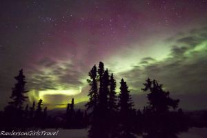 Trees standing against a yellow, green, and purple Northern Lights sky with stars and clouds