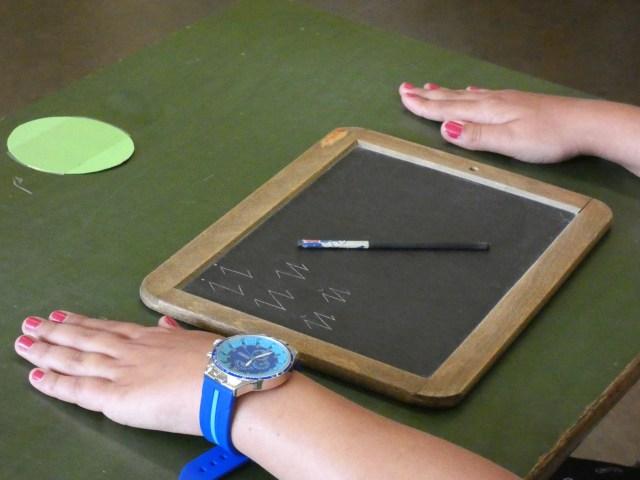 Schiefertafel, links und rechts Kinderhände