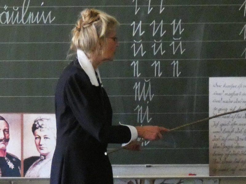 Fräulein Lehrerin erklärt die Schrift