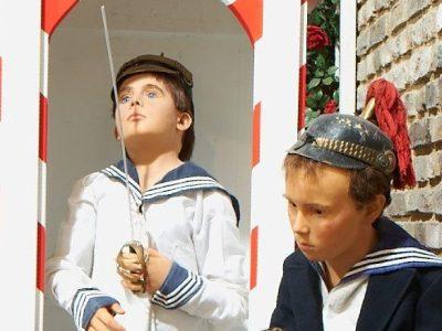Zwei Jungen im Matrosenanzug stehen vor einem Wachhäuschen