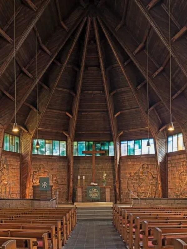 Innenraum der Kirche mit Bänken und riesigem Gewölbe
