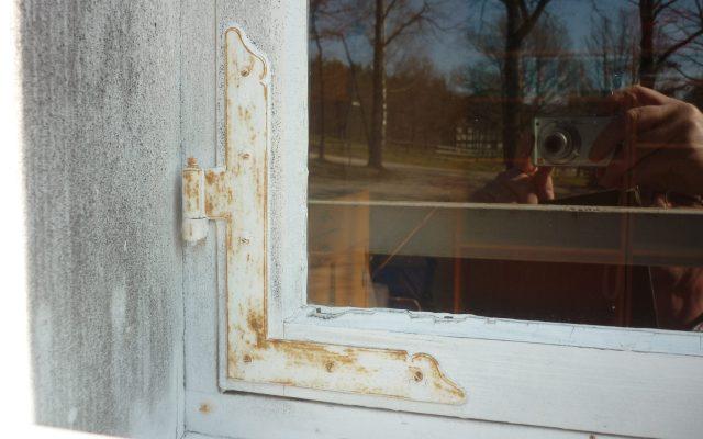 Ecke eines Holzfenster mit Metallbeschlag. In der Fensterscheibe spiegelt sich der Hintergrund